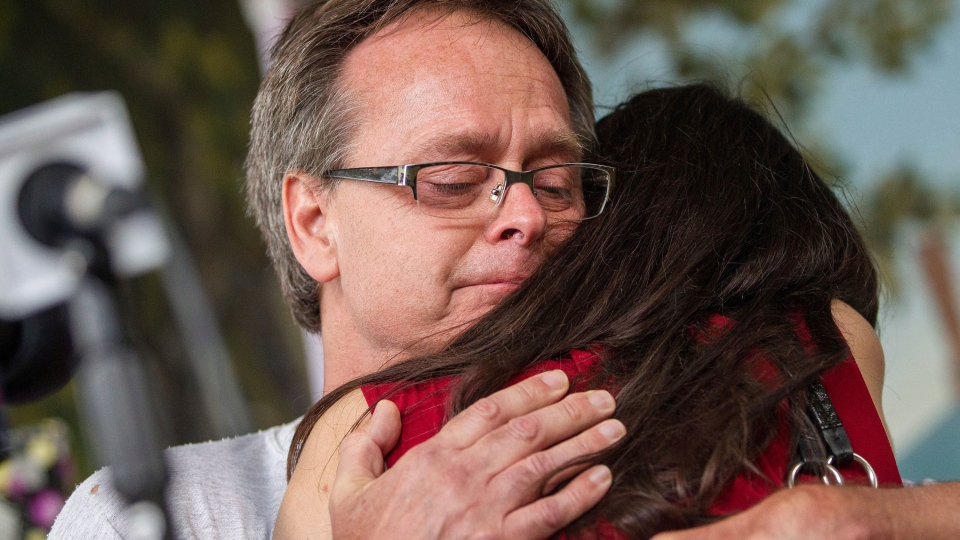 Marc Emery gets a hug from his wife Jodie during a press conference near the border crossing in Windsor, Ontario, Tuesday, August 12, 2014. (Geoff Robins / THE CANADIAN PRESS)