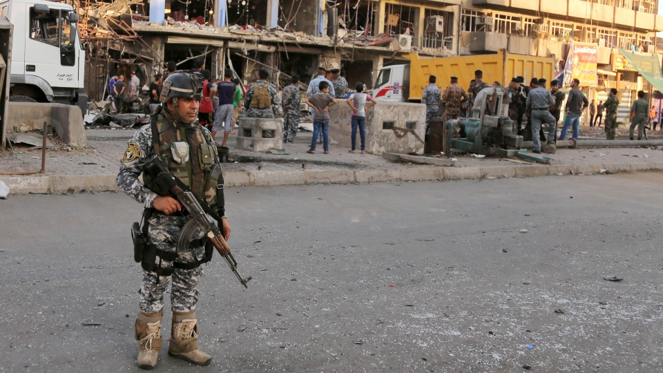 Iraqi policemen and civilians inspect the site of a car bomb attack near a restaurant in the southeastern district of New Baghdad, Iraq, Wednesday, Aug. 13, 2014. (AP / Karim Kadim)