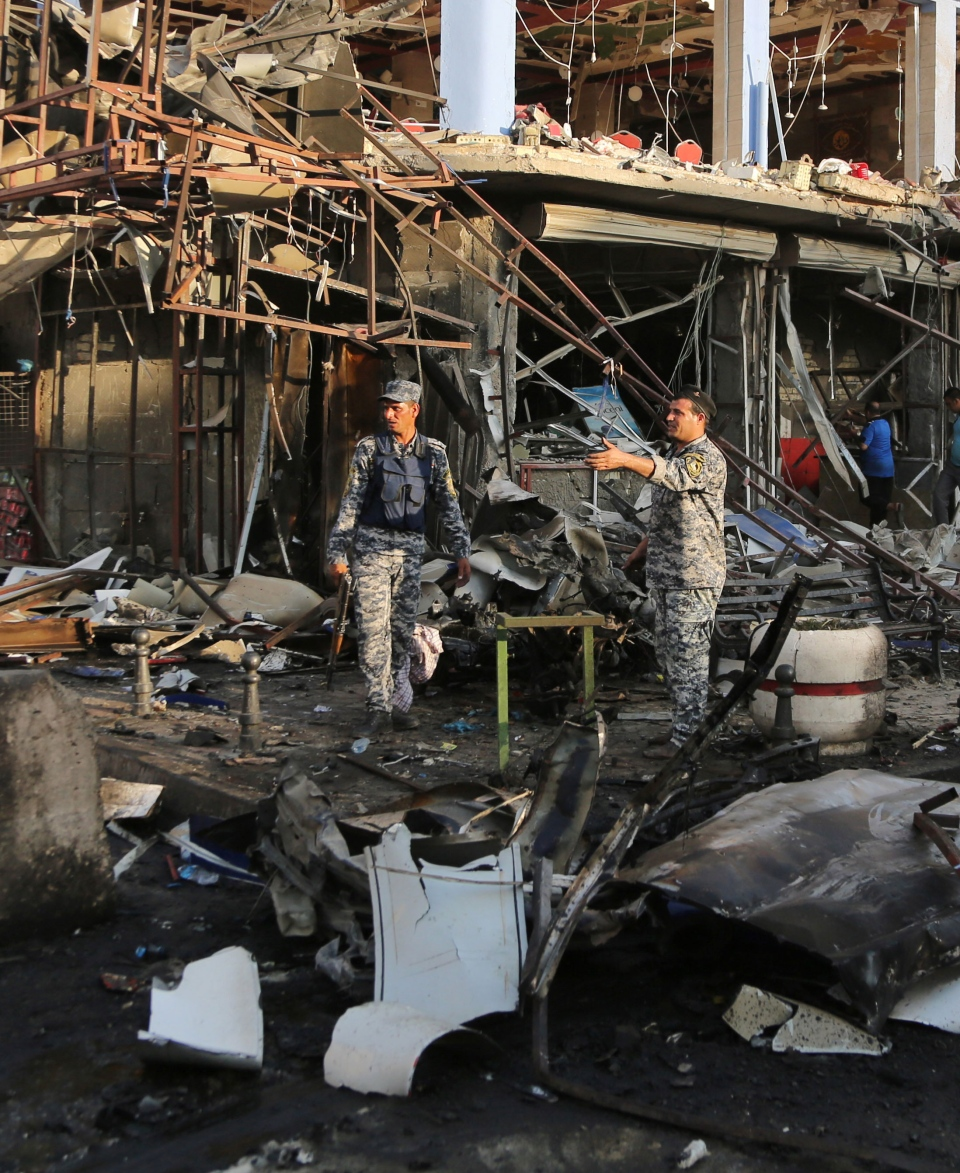 Iraqi policemen inspect the site of a car bomb attack near a restaurant in the southeastern district of New Baghdad, Iraq, Wednesday, Aug. 13, 2014. (AP / Karim Kadim)