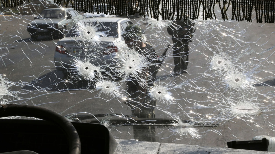 Pro-Russian rebels standing at a block-post on the outskirts of Donetsk seen through the bullet riddled windshield of a bus, eastern Ukraine, Wednesday, Aug. 13, 2014. (AP / Sergei Grits)