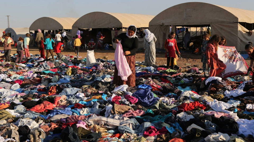 Displaced Iraqis from the Yazidi community look for clothes to wear among items provided by a charity organization at the Nowruz camp, in Derike, Syria, Tuesday, Aug. 12, 2014. (AP / Khalid Mohammed)