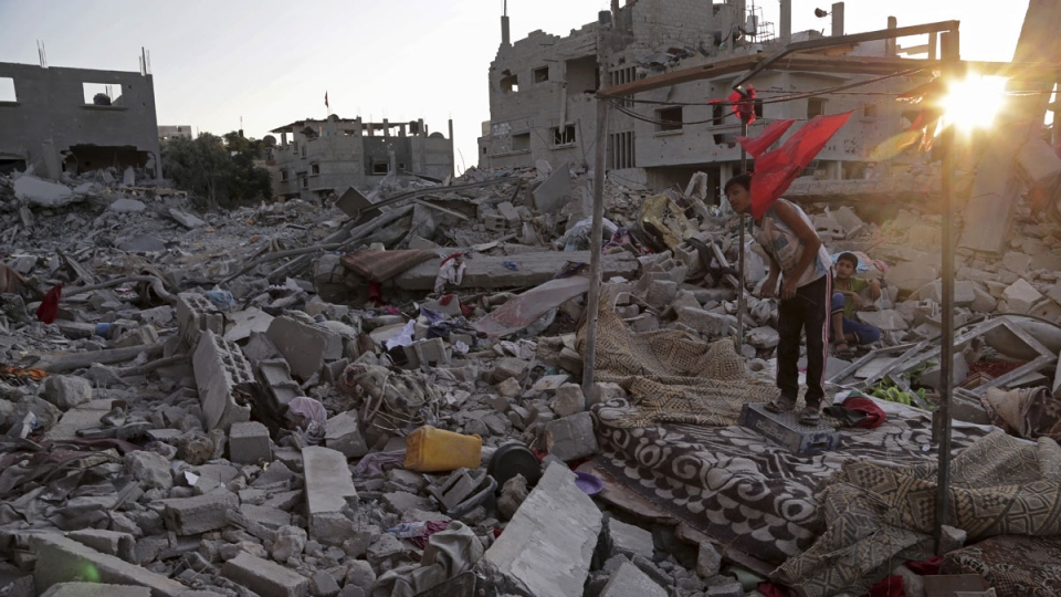 Ahmad and Mahmoud al Masri, sit during the sunset on the rubble of their family house, destroyed by Israeli strikes in the town of Beit Hanoun, in the northern Gaza Strip, Tuesday, Aug. 12, 2014. (AP / Adel Hana)