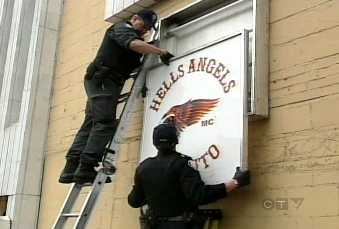 Toronto Police remove a sign from the suspected Hells Angels clubhouse on Eastern Avenue in downtown Toronto on Wednesday.