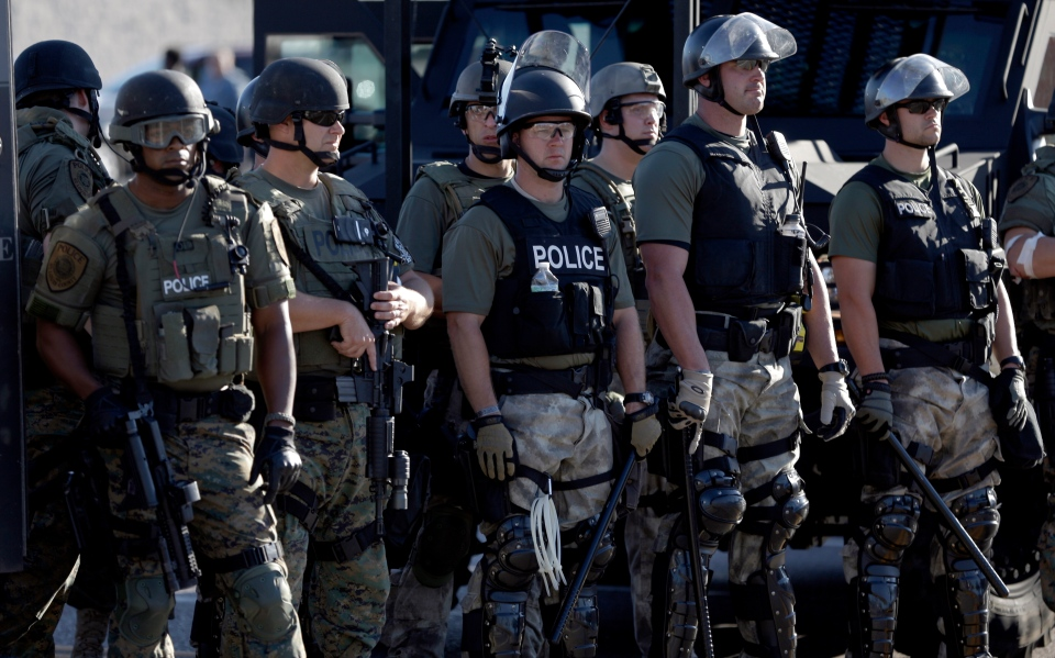 Police in riot gear watch protesters in Ferguson, Mo. on Wednesday, Aug. 13, 2014. (AP / Jeff Roberson)