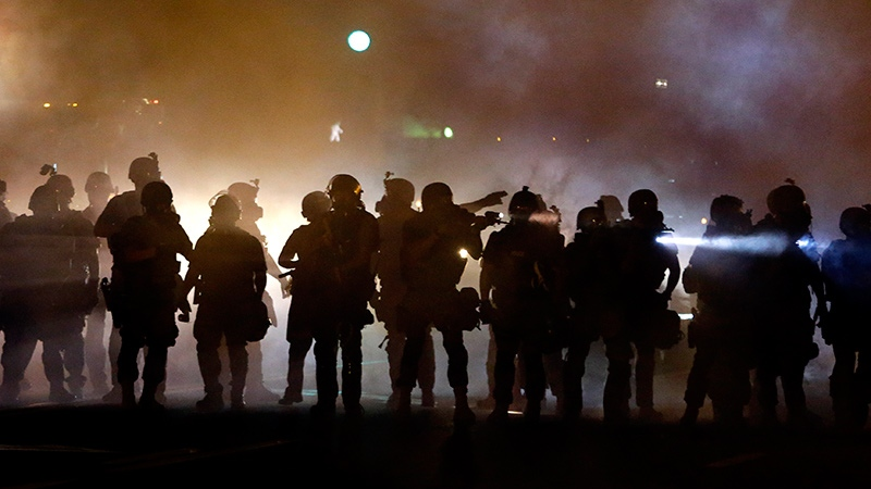 Police walk through a cloud of smoke as they clash with protesters in Ferguson, Mo. on Wednesday, Aug. 13, 2014. (AP / Jeff Roberson)