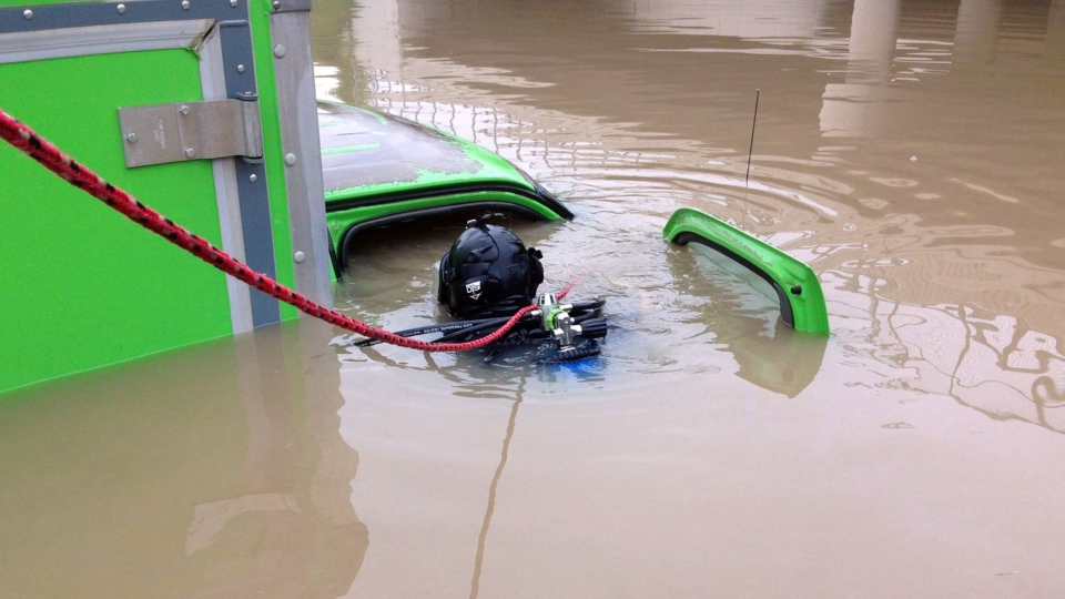 A diver with the Michigan State Police department's Underwater Recovery Unit inspects a vehicle submerged on a Detroit area freeway a day after heavy of rain Tuesday, Aug. 12, 2014. (Michigan State Police)