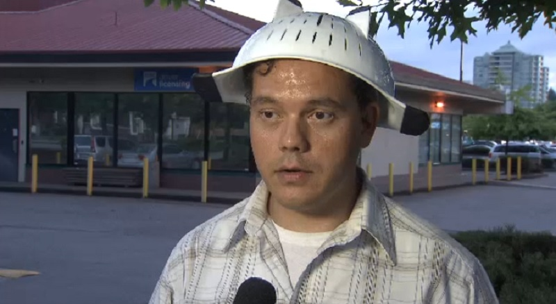 Obi Canuel is shown wearing a colander on his head in front of the ICBC office in British Columbia on Wednesday, August 13, 2014.