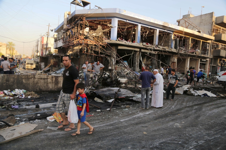 Civilians inspect the site of a car bomb attack near a restaurant in the southeastern district of New Baghdad, Iraq, Wednesday, Aug. 13, 2014. (AP / Karim Kadim)