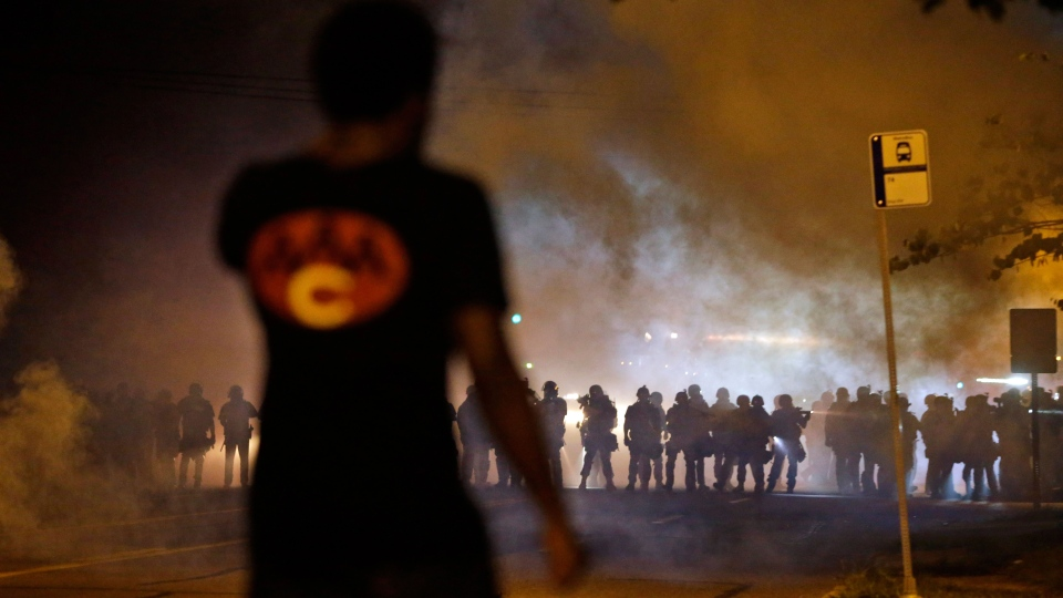 A man watches as police walk through a cloud of smoke during a clash with protesters in Ferguson, Mo. on Wednesday, Aug. 13, 2014. (AP / Jeff Roberson)