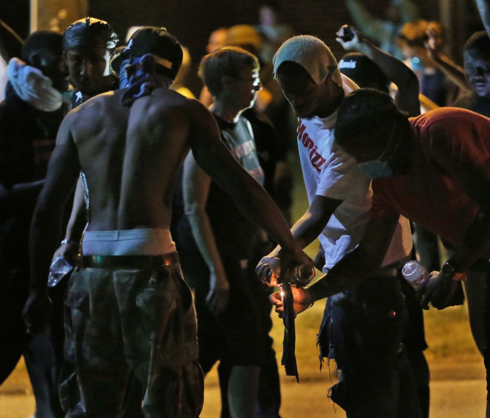Protesters try unsuccessfully to light a Molotov cocktail in Ferguson, Mo. on Wednesday, Aug. 13, 2014. (St. Louis Post-Dispatch, Chris Lee)