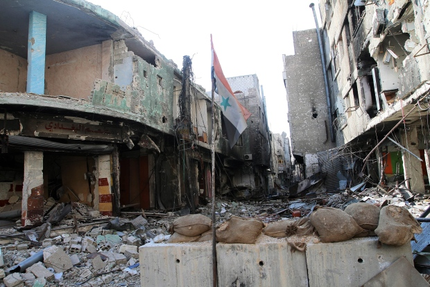 Syrian flag in rubble outside Damascus