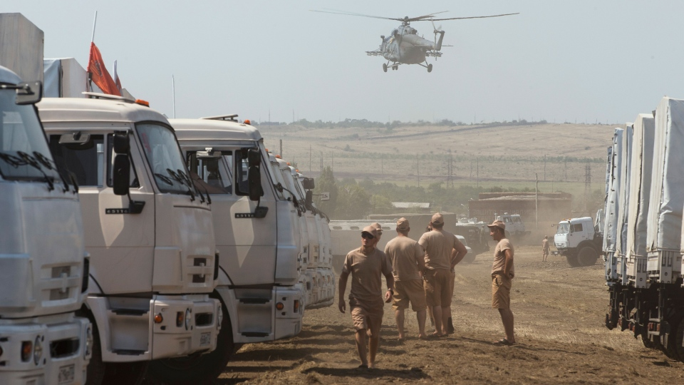 A Russian military helicopter prepares to land near a convoy of white trucks with humanitarian aid parked in a field about 28 kilometers from Ukrainian border in Rostov-on-Don region, Russia, Thursday, Aug. 14, 2014. (AP / Pavel Golovkin)