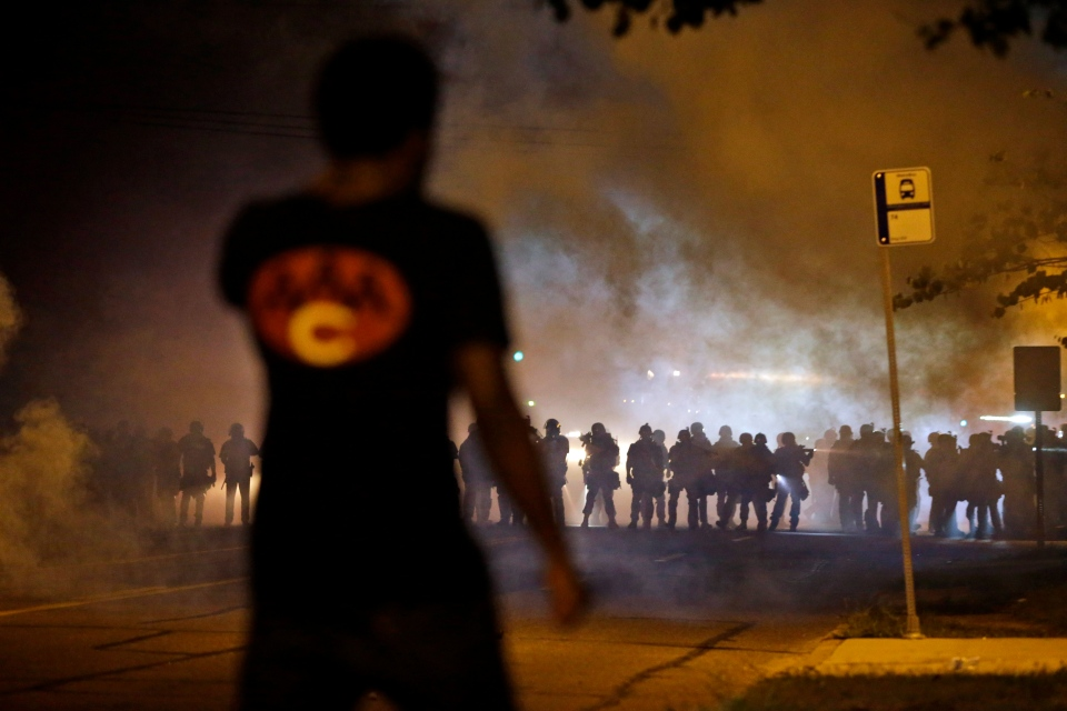 A man watches as police walk through a cloud of smoke during a clash with protesters, in Ferguson, Mo. on Wednesday, Aug. 13, 2014. (AP / Jeff Roberson)