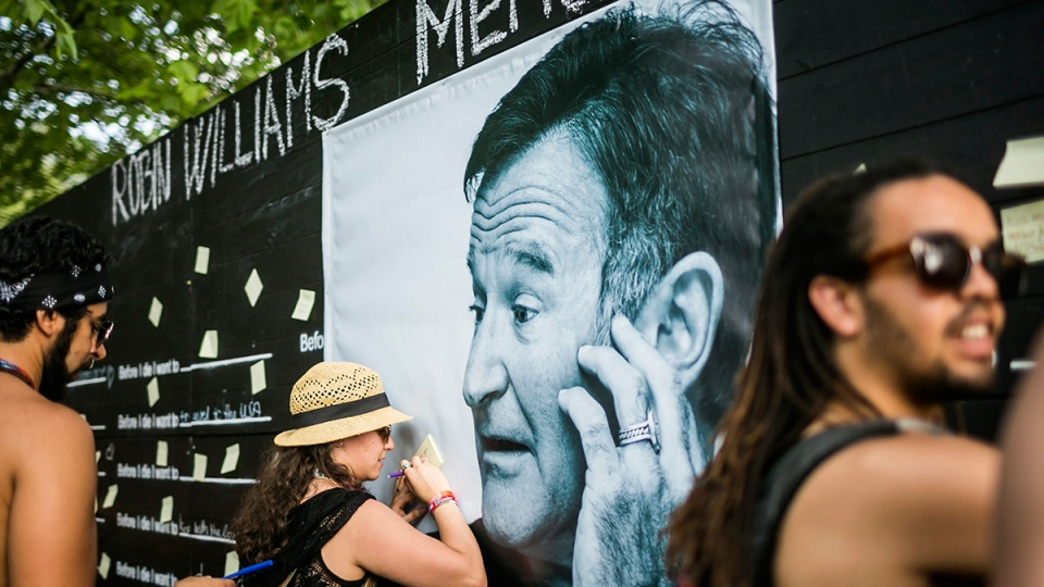 Festival goers pay tribute to the late actor Robin Williams, who died Tuesday, Aug. 11, at a makeshift memorial at the 22nd Sziget (Island) Festival on the Shipyard Island in Northern Budapest, Hungary, Wednesday, Aug. 13, 2014. (AP / MTI, Janos Marjai)