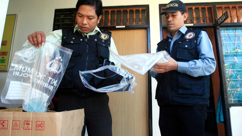 Indonesian forensic police officers view evidence related to the death of an American woman at a police station in Bali, Indonesia, Wednesday, Aug. 13, 2014. (AP / Firdia Lisnawati)