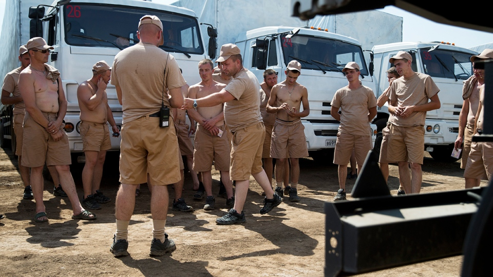 Drivers listen to instructions as they stand near their white trucks with humanitarian aid after parking in a field about 28 kilometers from Ukrainian border in Rostov-on-Don region, Russia, Thursday, Aug. 14, 2014. (AP / Pavel Golovkin)