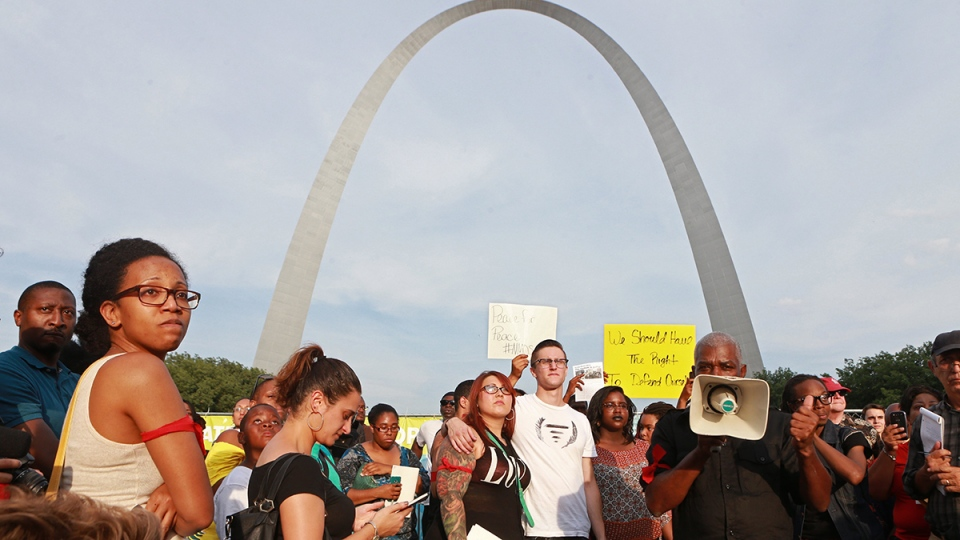 People gather in a park near the Gateway Arch for a moment of silence for Michael Brown, in St. Louis, Thursday, Aug. 14, 2014. (AP / St. Louis Post-Dispatch, Christian Gooden)