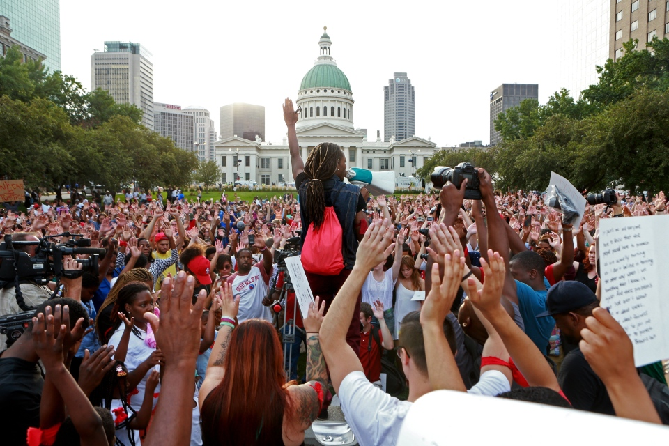 Jay Mitchell, of Pagedale, Mo., speaks and solicits a response of hands in the air from the crowd in St. Louis during a peace vigil and moment of silence for Michael Brown, Thursday, Aug. 14, 2014. (St. Louis Post-Dispatch, Christian Gooden)