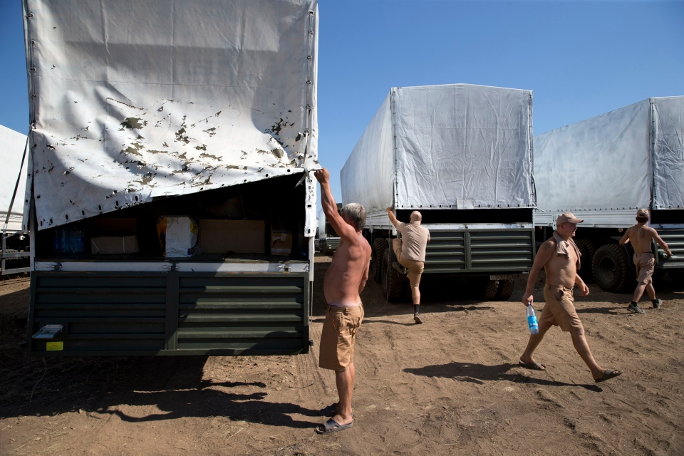 Drivers prepare to show cargos to journalists in a field where the aid convoy is parked in Voronezh, about 30 kilometres from Ukrainian border, Rostov-on-Don region, Russia on Friday, Aug. 15, 2014. (AP / Pavel Golovkin)