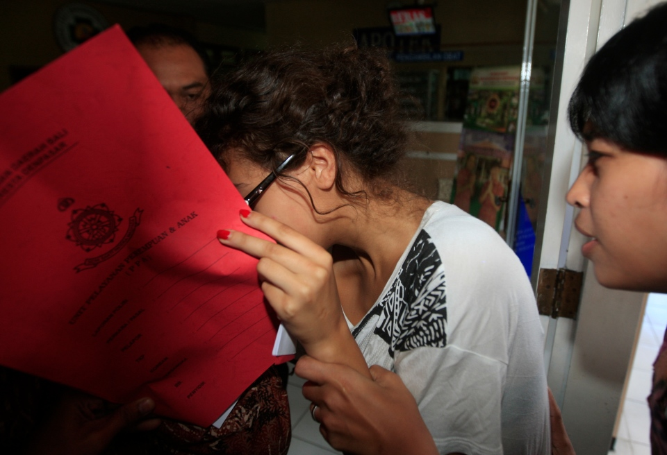 Heather Mack, covering her face, is led to a hospital for a medical check by Indonesian police officers in relation to the death of her mother Sheila von Wiese-Mack in Bali, Indonesia on Friday, Aug. 15, 2014. (AP / Firdia Lisnawati)