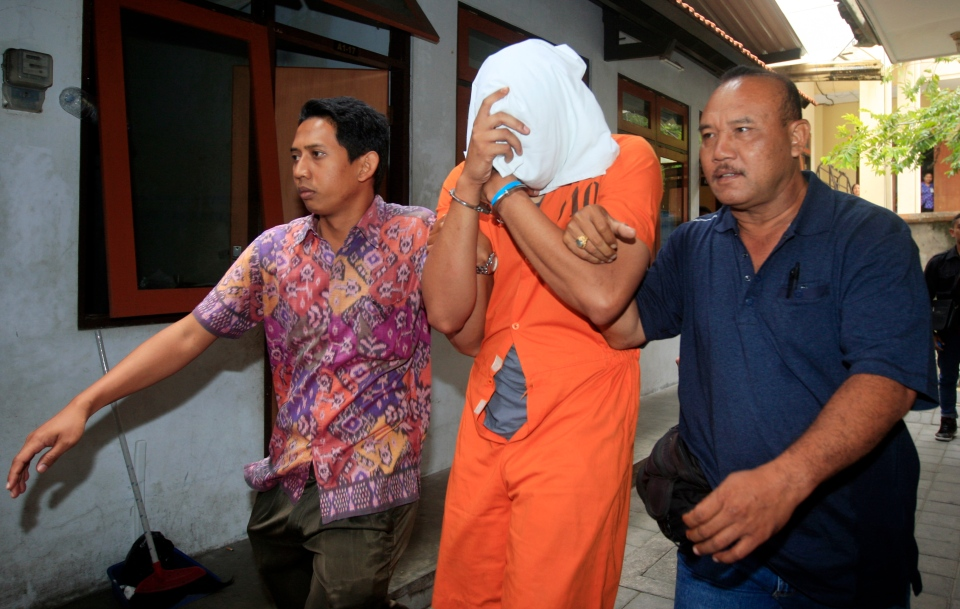 Indonesian police officers escort Tommy Schaefer, centre, covering his face, to a hospital for medical check Friday, Aug. 15, 2014. (AP / Firdia Lisnawati)