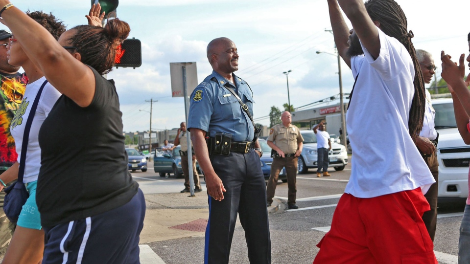 Capt. Ronald Johnson of the Missouri Highway Patrol smiles at demonstrators march along West Florissant Avenue in Ferguson, Mo., on Thursday, Aug. 14, 2014. (St. Louis Post-Dispatch, David Carson)