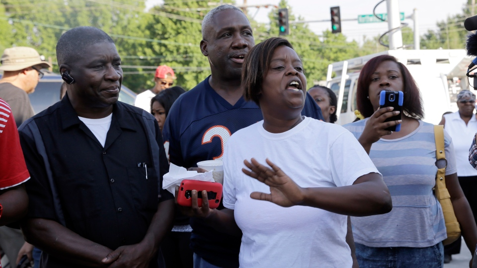 People react after Ferguson Police Chief Thomas Jackson releases the name of the the officer accused of fatally shooting Michael Brown, an unarmed black teenager in Ferguson, Mo., Friday, Aug. 15, 2014. (AP / Jeff Roberson)
