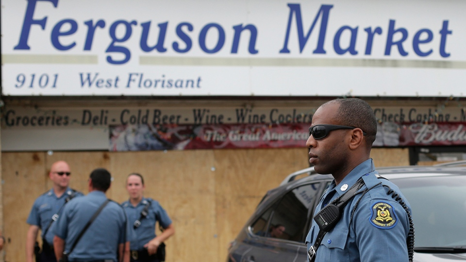 Missouri Highway Patrol troops stand watch outside a market where Michael Brown allegedly stole some cigars before being killed by police nearly a week ago in Ferguson, Mo., Friday, Aug. 15, 2014. (AP / Charlie Riedel)