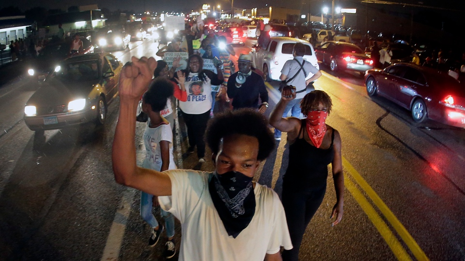 Protesters march down the middle of a street, Friday, Aug. 15, 2014, in front of a convenience store that was looted and burned following the shooting death of Michael Brown by police nearly a week ago in Ferguson, Mo. (AP / Charlie Riedel)