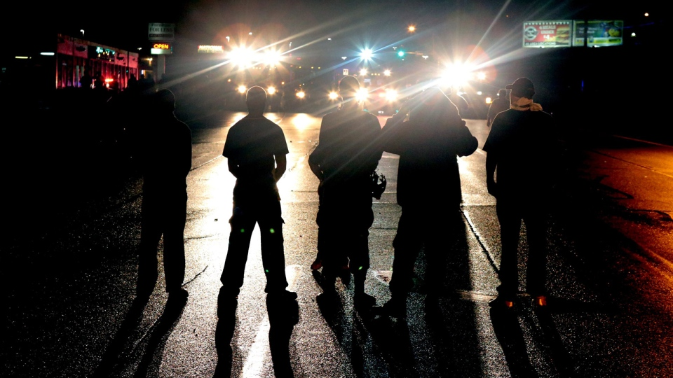 Against a backdrop of flood lights from police tactical vehicles, protestors stand their ground in the middle of West Florissant Avenue in Ferguson, refusing to leave despite police orders early Saturday, Aug. 16, 2014. (AP / St. Louis Post-Dispatch, Robert Cohen)