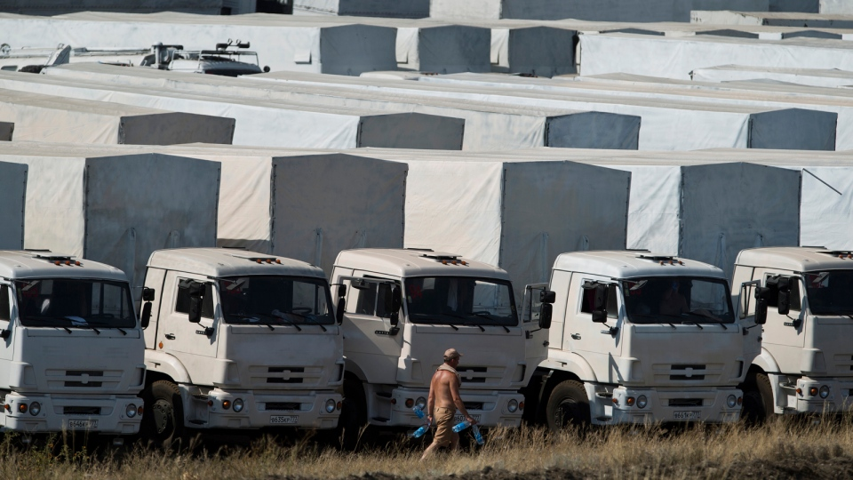 A driver carries empty water bottles as he walks past trucks forming part of an aid convoy parked in a field about 28 kilometers from the Ukrainian border, near Kamensk-Shakhtinsky, Rostov-on-Don region, Russia, Saturday, Aug. 16, 2014. (AP / Pavel Golovkin)