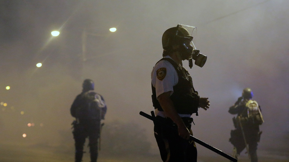 Law enforcement officers wait to advance Sunday, Aug. 17, 2014, after firing tear gas to disperse a crowd protesting the shooting of teenager Michael Brown last Saturday in Ferguson, Mo. (AP / Charlie Riedel)