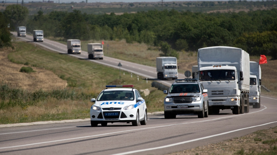Trucks forming part of an aid convoy destined for Ukraine are escorted by a police vehicle as they travel on a road to the border control point in the Russian town of Donetsk, in the Rostov-on-Don region, Russia, Sunday, Aug. 17, 2014. (AP / Pavel Golovkin)
