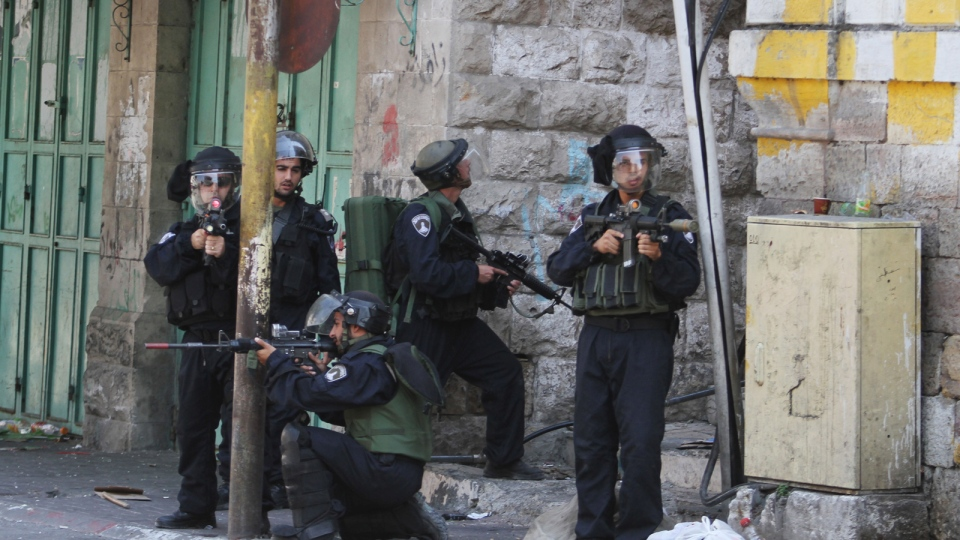 Israeli soldiers aim hold their weapons during clashes with Palestinians following a protest against the recent Israeli military action over Hamas in Gaza, in the West Bank city of Hebron on Friday, Aug. 15 , 2014. (AP / Nasser Shiyoukhi)