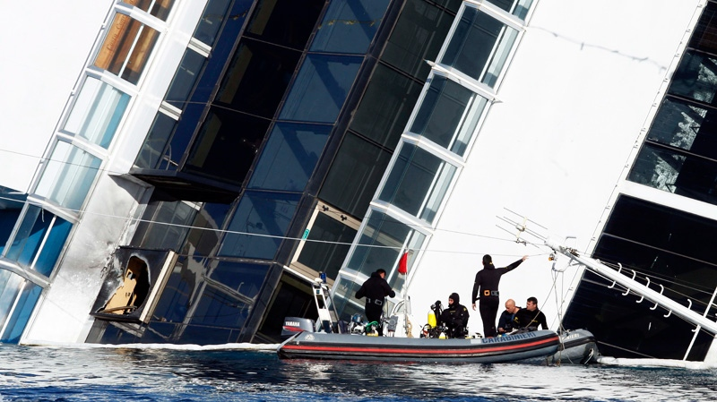 Italian Carabinieri divers work next to the grounded cruise ship Costa Concordia off the Tuscan island of Giglio, Italy, Saturday, Jan. 21, 2012. (AP / Pier Paolo Cito)