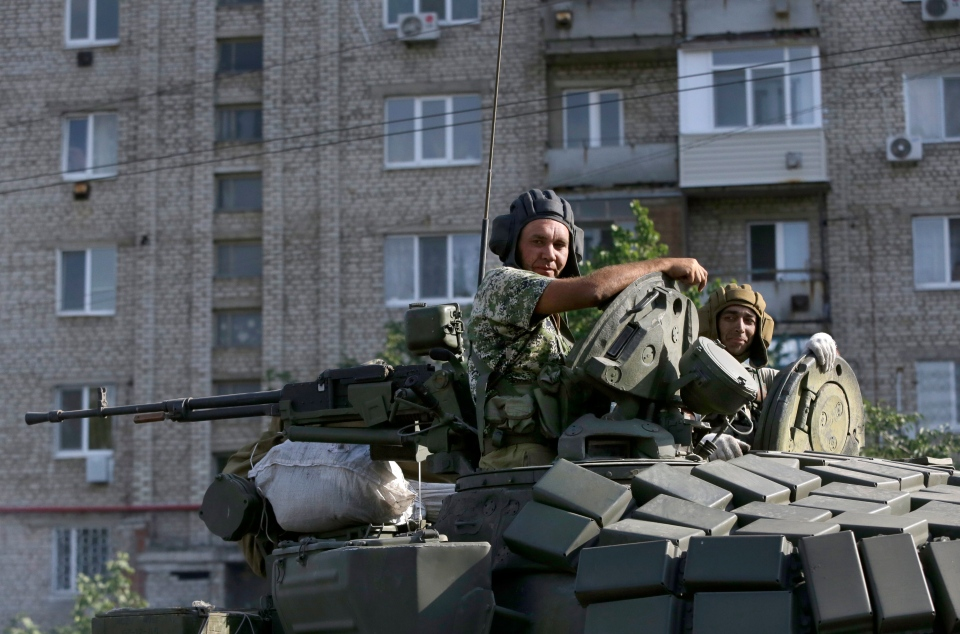 Pro-Russian rebels ride on a tank in the town of Krasnodon, eastern Ukraine, Sunday, Aug. 17, 2014. A column of several dozen heavy vehicles, including tanks and at least one rocket launcher, rolling through rebel-held territory on Sunday.(AP Photo/Sergei Grits)