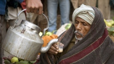 A fruit seller takes a cup of tea at a fruit market in Mundera on the outskirts of Allahabad, India, Tuesday, Dec. 18, 2007. (AP Photo/ Rajesh Kumar Singh)