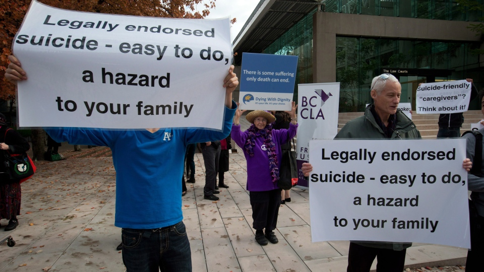 A woman, centre, holds a sign in support of assisted suicide as a group of people opposed to it demonstrate outside the B.C. Court of Appeal after the court overturned a lower court ruling that said Canada's assisted-suicide ban violated the charter rights of gravely ill Canadians, in Vancouver, B.C., on Thursday October 10, 2013. (Darryl Dyck / THE CANADIAN PRESS)
