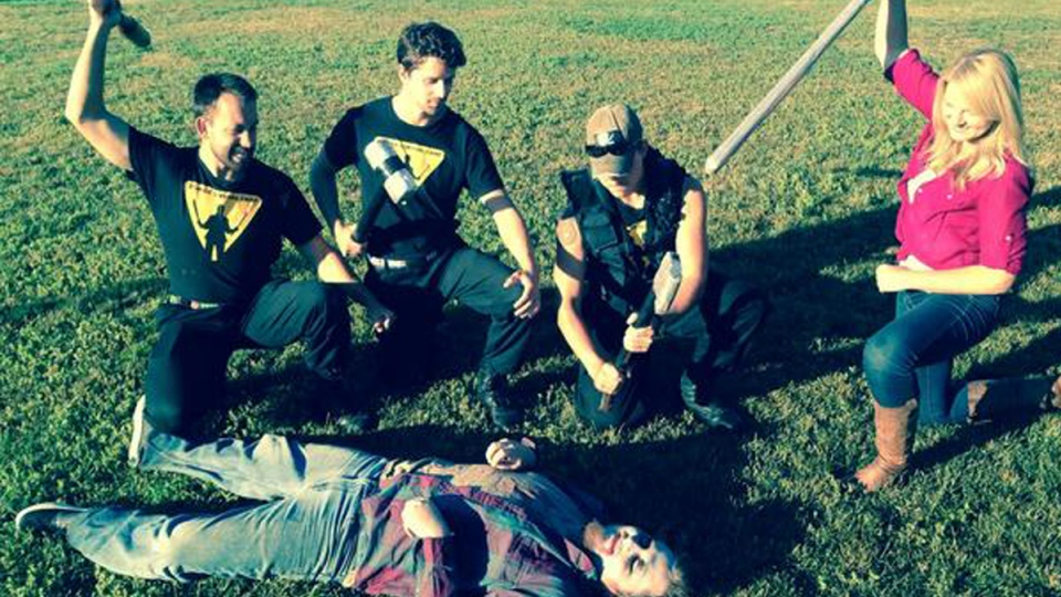 Zombie Survival Camp instructors pose over a 'zombie' with CTV Winnipeg reporter Karen Rocznik on Monday, August 11, 2014. (Twitter / Karen Rocznik)