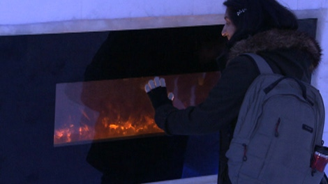 A visitor warms her hands on a fireplace at Snow Village Canada in Montreal's Parc Jean-Drapeau, which features 30 rooms, an ice bar, a snow labyrinth, snow sculptures, a restaurant and a chapel.