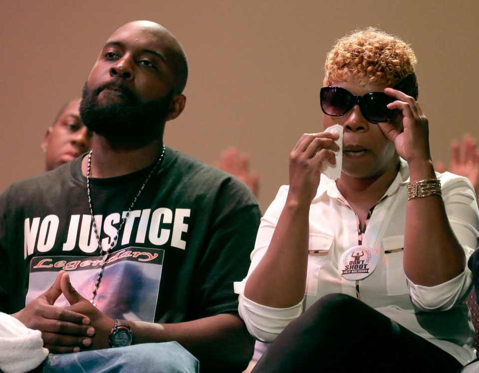 Parents of Michael Brown, Michael Brown Sr. and Lesley McSpadden listen to a speaker during a rally Sunday, Aug. 17, 2014, for their son who was killed by police last Saturday in Ferguson, Mo. (AP / Charlie Riedel)