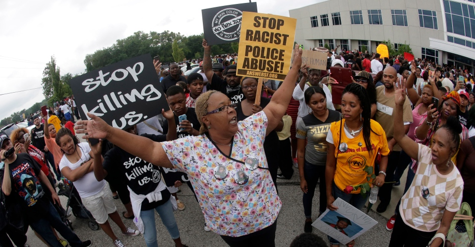 Helen Shaw talks to people during a rally outside Greater Grace Church, Sunday, Aug. 17, 2014, for Michael Brown Jr., who was killed by police, last Saturday in Ferguson, Mo. (AP / Charlie Riedel)