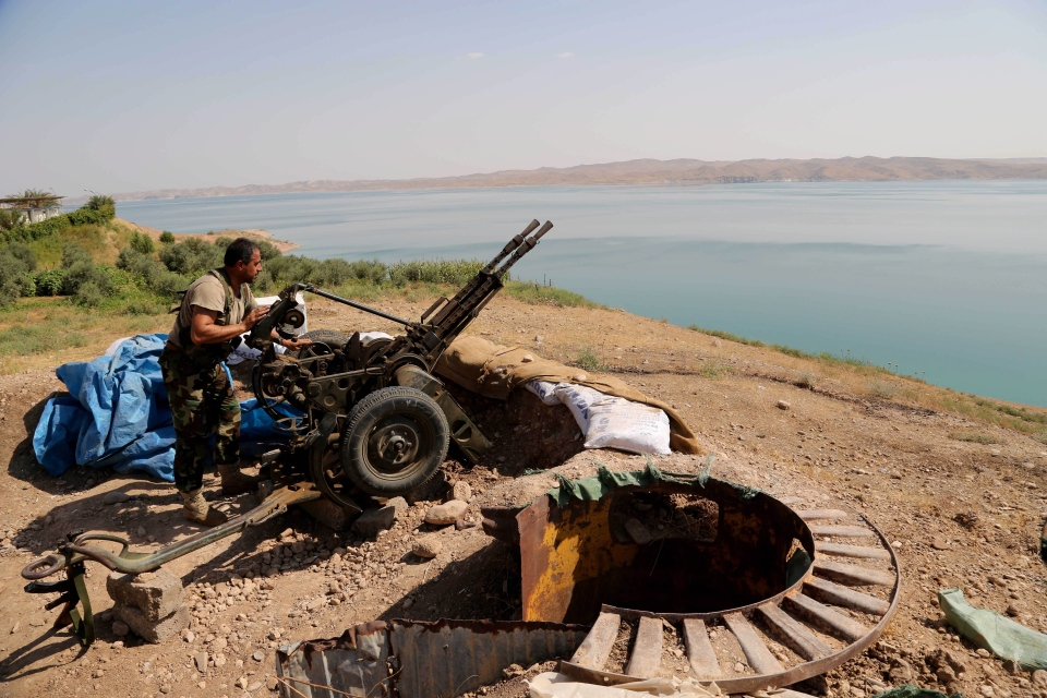 A Kurdish peshmerga fighter prepares his weapon at his combat position near the Mosul Dam at the town of Chamibarakat outside Mosul, Iraq, Sunday, Aug 17, 2014.(AP / Khalid Mohammed)