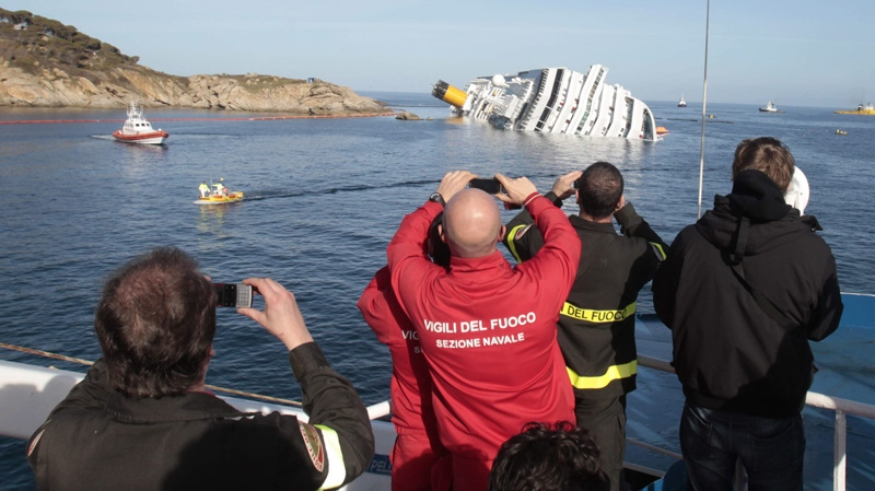 Firefighters take pictures of the cruise ship Costa Concordia ship, off the Tuscan island of Giglio, Italy, Saturday, Jan. 21, 2012. (AP Photo/Gregorio Borgia)