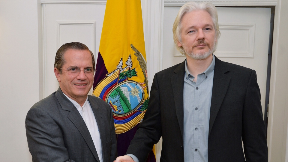 Ecuador's Foreign Minister Ricardo Patino, left, shakes hands with WikiLeaks founder Julian Assange after a press conference inside the Ecuadorian Embassy in London, Monday Aug. 18, 2014, where Assange confirmed he 'will be leaving the embassy soon.' (AP / John Stillwell, POOL)