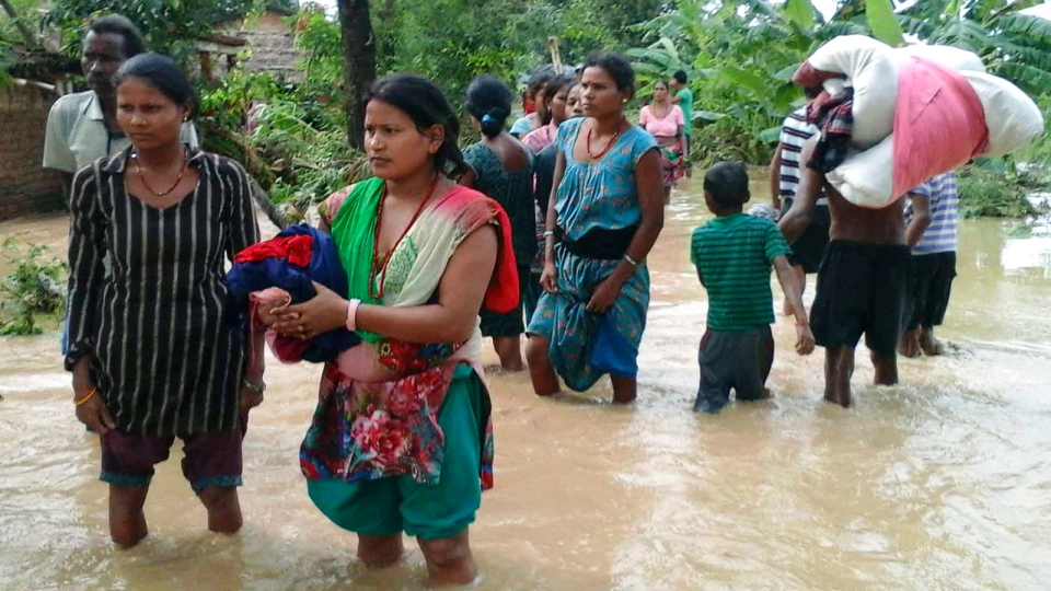 Nepalese villagers carry their belongings while wading through a flooded street to move to safer ground, at Bardia, in western Nepal, Friday, Aug. 15, 2014 photo. (AP / Bhabuk Yogi)