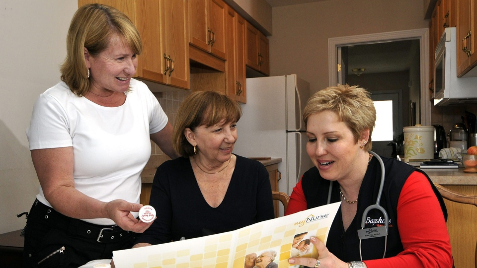 In this undated photo, Beverly Amodeo (centre) discusses the results of her in-home health consultation with registered nurse Polina Philip (right) and daughter Suzanne Amodeo (left) in her home in Newmarket, Ont. (Bayshore Home Health / The Canadian Press Images)