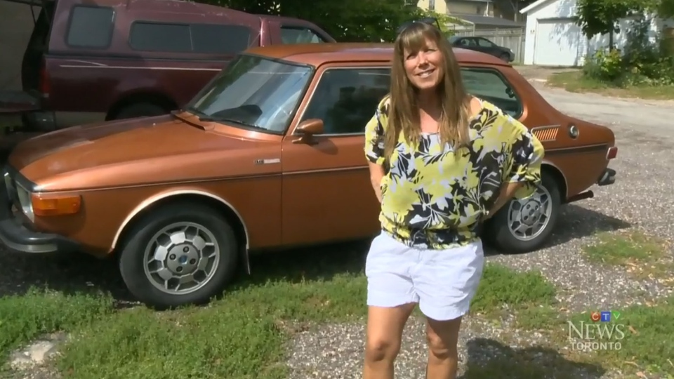 Joanie Wadden stands with her 1973 Saab 99 EMS in Kitchener, Ont. on Sunday, Aug. 17, 2014.