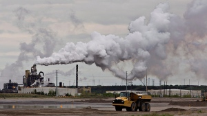 A dump truck works near the Syncrude oil sands extraction facility near the town of Fort McMurray, Alta. on Sunday, June 1, 2014. (Jason Franson / THE CANADIAN PRESS)