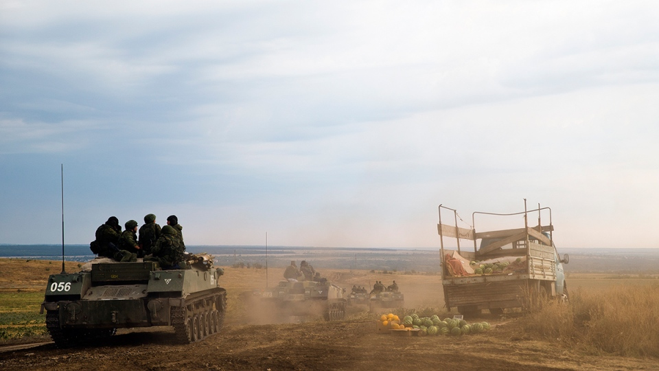Several Russian APC passes near watermelon plantation's field-market, right, in about 10 kilometres from the Russia-Ukrainian border control point at Russian town of Donetsk, Rostov-on-Don region, Russia, Monday, Aug. 18, 2014. (AP / Pavel Golovkin)